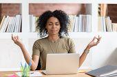Calm Black Businesswoman Taking Break Meditating Doing Yoga At Work poster