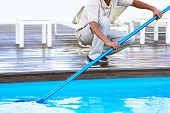 Pool Cleaner During His Work. Hand African Hotel Staff Worker Cleaning The Pool. poster