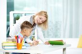 stock photo of tutor  - Portrait of smart tutor with pencil correcting mistakes in pupil - JPG