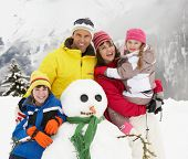 stock photo of family ski vacation  - Family Building Snowman On Ski Holiday In Mountains - JPG