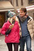 Couple Walking Along Snowy Town Street In Ski Resort