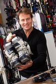 stock photo of ski boots  - Sales Assistant With Ski Boots In Hire Shop - JPG