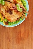 whole roasted chicken with lettuce, grapes, oranges and spices on blue plate on wooden background cl