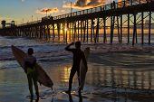 Surfistas ao pôr do sol em Oceanside, Califórnia, admiram o pôr do sol através do velho cais de madeira.