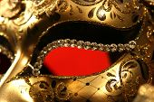 stock photo of mardi-gras  - Details of Venetian mask on red background - JPG