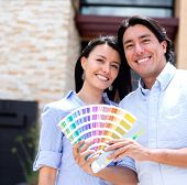 Couple painting their house and holding a Pantone