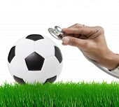 soccer football on green grass field with hand and stethoscope isolated on white