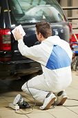 auto mechanic worker preparing car body for polishing at automobile repair and renew service station