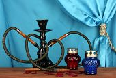 foto of shisha  - hookah on a wooden table on a background of blue curtain close - JPG