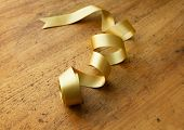 Gold ribbon nicely uncurled, on old wooden desk. Preparation for gift wrapping.