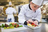 stock photo of fruit bowl  - Chef putting a strawberry in the fruit salad in the kitchen - JPG