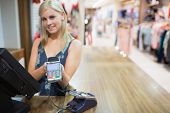 Woman holding credit card mahine in clothing store