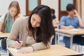stock photo of exams  - Woman doing an exam in exam hall in college - JPG