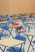 Student leaning on desk napping in exam hall of college
