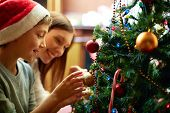stock photo of youngster  - Portrait of happy boy in Santa cap decorating Christmas tree - JPG