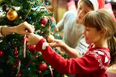 stock photo of pullovers  - Portrait of happy girl decorating Christmas tree - JPG