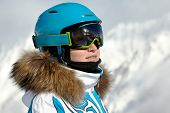 Portrait of young woman in ski suit, helmet and sunglasses, mountains and skilift supports reflected