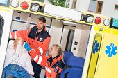 Paramedics checking IV drip patient in ambulance treatment aid emergency