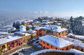 Aerial view on small town, houses and roofs covered with snow at Diano D'Alba in Piedmont, Northern