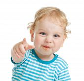 funny curly child with dirty lips pointing by finger directly to camera