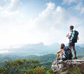 Hikers with backpacks enjoying valley view from top of a mountain