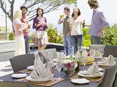 Mesa de comedor fino ajuste con amigos disfrutando de bebidas en el fondo