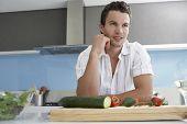 Jovem bonito olhando para longe enquanto encostado no balcão da cozinha ao lado de legumes no tabuleiro