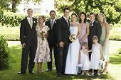 Full length portrait of happy bride and groom standing with guests in garden