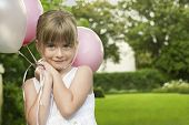 Portrait of cute little bridesmaid holding balloons in garden