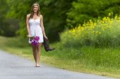 A brunette model walking down a country road