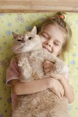 The little girl hugging the cat lying on a mattress on the floor