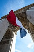 stock photo of charles de gaulle  - Arc de Triomphe with French flag hanging from vaulted ceiling inside the arch - JPG