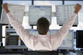 image of multitasking  - Rear view of stock trader with hands raised looking at multiple computer screens - JPG