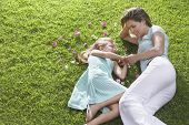 Mother and daughter lying on lawn with flowers strewn nearby