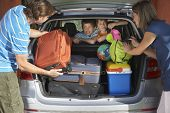 picture of carry-on luggage  - Two young sons watching parents load luggage in car trunk - JPG