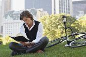 Full length of handsome young businessman reading book by bicycle in park