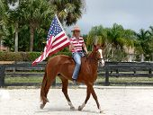 picture of bareback  - US Patriotic holiday image of woman riding horse bareback carrying the American flag