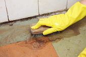 Hand in yellow glove cleaning dirty filthy floor with brush indoors