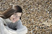 stock photo of herne bay beach  - Portrait of happy young woman wearing sweater sitting at beach - JPG
