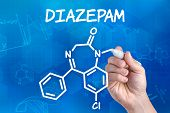 hand with pen drawing the chemical formula of Diazepam