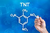 hand with pen drawing the chemical formula of TNT