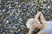 High angle view of beautiful young woman with eyes closed lying on pebbles at beach