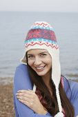 image of herne bay beach  - Portrait of happy young woman wearing knit hat standing on beach - JPG