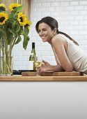 Side view of happy young woman with wineglass leaning on counter at home
