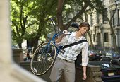 Young businessman carrying bicycle outdoors