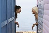 Side view of happy female friends looking at each other while leaning on balustrade of beach house