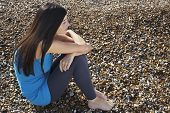 stock photo of herne bay beach  - Full length of thoughtful young woman sitting on pebbles at beach - JPG