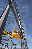 Manual worker working from cherry picker on steel framing structure