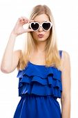 Beautiful woman in blue dress using sunglasses with a hearth shape, isolated over white background