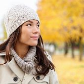 stock photo of thoughtfulness  - Thinking autumn woman looking at fall forest smiling happy walking in colorful autumn foliage outdoors - JPG